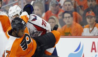 Philadelphia Flyers' Wayne Simmonds, left, is upended by Washington Capitals' T.J. Oshie during the first period of Game 3 in the first round of the NHL Stanley Cup hockey playoffs, Monday, April 18, 2016, in Philadelphia. (AP Photo/Matt Slocum)