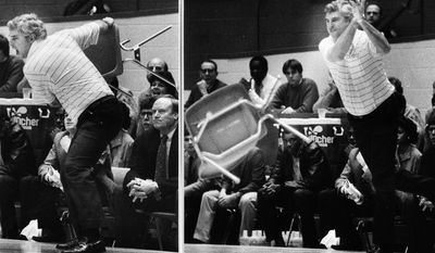 FILE - In this Feb. 23, 1985, file photo, Indiana coach Bob Knight winds up and pitches a chair across the floor during Indiana's 72-63 loss to the Purdue in Bloomington, Ind. There are a few things you won't find among the many items Knight is putting on the auction block over the next two months in New York, like the chair he launched across the Assembly Hall court five minutes into a game to clear up any confusion over what he thought of the officiating. (AP Photo/File)