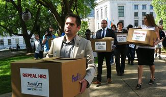 State Rep. Chris Sgro, D-Guilford, who is also executive director of Equality NC, leads a group carrying petitions calling for the repeal of House Bill 2 to Gov. Pat McCrory's office at the state Capitol building Monday, April 25, 2016, in Raleigh, N.C. (Chuck Liddy/The News & Observer via AP)