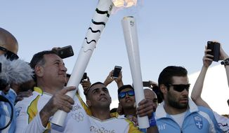 Syrian refugee Ibrahim Al-Hussein, 27, center, freestyle swimmer, basketball player and former judo wrestler receives the Olympic flame from the head of Greece's Olympic Committee, Spyros Capralos, at the Elaionas camp that is home to about 1,500 refugees and other migrants, in Athens on Tuesday, April 26, 2016. The flame arrives in Brazil on May 3, and will be relayed across the vast country by about 12,000 torchbearers before the Aug. 5 opening ceremony in Rio de Janeiro's Maracana Stadium. (AP Photo/Thanassis Stavrakis)