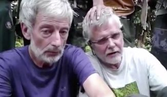 This image made from undated militant video, shows Canadians John Ridsdel, right, and Robert Hall. Canada's Prime Minister Justin Trudeau confirmed that the decapitated head of a Caucasian male recovered Monday, April 25, 2016, in the southern Philippines belongs to Ridsdel, who was taken hostage by Abu Sayyaf militants in September 2015. (Militant Video via AP Video)