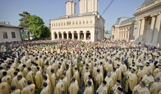 Priests and believers stand outside the Patriarchal Cathedral after an Orthodox Palm Sunday pilgrimage in Bucharest, Romania, Saturday, April 23, 2016. According to local media more than 800 priests and thousands of Orthodox worshippers marched through the Romanian capital and major cities ahead of Palm Sunday. (AP Photo/Vadim Ghirda)