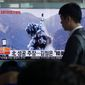 People in South Korea watch a TV news program showing an image published Sunday in North Korea's Rodong Sinmun newspaper of North Korea's ballistic missile that the North claimed to have launched from underwater. (Associated Press) ** FILE **