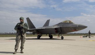 A U.S. military policeman stands in front of a U.S. Air Force F-22 Raptor fighter jet  at the Siauliai airbase, some 230 km (144 miles) east of the capital Vilnius, Lithuania, Wednesday, April 27, 2016. Two US F-22 fighter, which are part of the Operation Atlantic Resolve, a U.S. commitment to NATO's collective security and regional stability, arrived from their base in Britain as a show of force to help Baltic members protect their borders with Russia. (AP Photo/Mindaugas Kulbis)