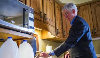 In this April 18, 2016, file photo, Michigan Gov. Rick Snyder fills jugs with filtered tap water at Cheryl Hill's house, in Flint, Mich. (Jake May/The Flint Journal-MLive.com via AP File)