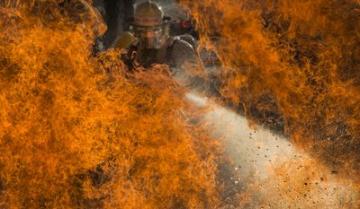 Hon. mention in the Pictorial category: Three military students assigned to the 312th Training Squadron battle a fire during a liquid fire scenario at the Louis F. Garland Department of Defense Fire Academy, Oct. 19, 2015. During liquid fire training, the students rotate through three-man iterations of low and high fires while moving through water. The joint DOD school is comprised of Air Force, Army, Navy, Marine and civil service students. IMAGE: STAFF SGT. VERNON YOUNG JR., USAF