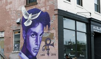 A mural honoring the late rock star Prince adorns a building in the Uptown area of Minneapolis Thursday, April 28, 2016, Prince died last week at his Paisley Park home at the age of 57. An investigation into his death continues. (AP Photo/Jim Mone)