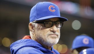FILE - In this April 21, 2016 file photo, Chicago Cubs manager Joe Maddon stands in the dugout during a baseball game against the Cincinnati Reds in Cincinnati. Expectations for both Chicago baseball teams this year are high as the Cubs and White Sox lead their perspective leagues three weeks into the season. (AP Photo/John Minchillo, File)