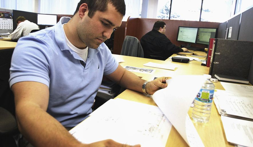In this April 5,2016 photo, Eisenmann Corp. project manager Joe Schlesinger checks a schematic drawing at the company's headquarters in Crystal Lake, Ill. For some companies that employ a large segment of millennials in McHenry County, they've found that a clearly marked career path, engagement and perks providing the work-life balance many millennial workers are known to desire all can draw them to suburban locations and keep them there. (H. Rick Bamman/Northwest Herald via AP) CHICAGO TRIBUNE OUT, MANDATORY CREDIT