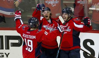 Washington Capitals T.J. Oshie (77) celebrates his second goal against Pittsburgh Penguins with teammates Nicklas Backstrom (19) and Karl Alzner (27), during the third period of Game 1 in an NHL hockey Stanley Cup Eastern Conference semifinal series Thursday, April 28, 2016, in Washington. The Capitals won 4-3 in overtime. (AP Photo/Pablo Martinez Monsivais)