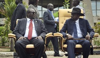 South Sudan's First Vice President Riek Machar, left, looks across at President Salva Kiir, as the two sit to be photographed following the first meeting of a new transitional coalition government, in the capital Juba, South Sudan Friday, April 29, 2016. The two leaders have formed a transitional coalition government including politicians from the government and the armed opposition who have been at war for the last two and a half years. (AP Photo/Jason Patinkin)