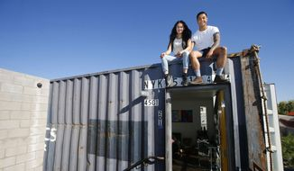 In this Wednesday, March 16, 2016, photo, Patrick Tupas, right, with his wife, Maria Real-Tupas, sit on the roof of their shipping container apartment, in Phoenix. In the Containers on Grand project, the apartments are designed in a way that retains the corrugated metal exteriors. Each unit is made of two containers, but inside there are no signs of the cargo hauling days. (AP Photo/Ross D. Franklin)