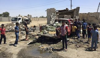 Civilians inspect the scene of car bombing at an open-air market selling fruit, vegetables and meat in Baghdad's southeast suburb of Nahrawan, Iraq, Saturday, April 30, 2016. (AP Photo/Ali Abdul Hassan)
