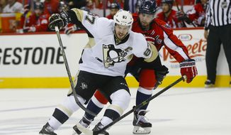 Pittsburgh Penguins center Sidney Crosby (87) and Washington Capitals defenseman Matt Niskanen (2) chase down the puck during the first period of Game 2 in an NHL hockey Stanley Cup Eastern Conference semifinals Saturday, April 30, 2016 in Washington. (AP Photo/Pablo Martinez Monsivais)