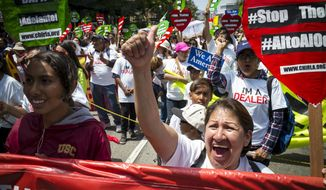 Hundreds of May Day marchers chanting slogans and carrying signs take to the streets of Los Angeles, calling for immigrant and worker rights and decrying what they see as hateful presidential campaign rhetoric, Sunday, May 1, 2016. (David Crane/Los Angeles Daily News via AP)