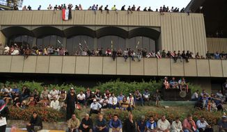Supporters of Shiite cleric Muqtada al-Sadr attend a sit-in before leaving Baghdad's highly fortified Green Zone, Sunday, May 1, 2016. Anti-government protesters temporarily ended their mass demonstration in Baghdad's Green Zone on Sunday and began an orderly withdrawal a day after tearing down walls around the government district and invading parliament. (AP Photo/Karim Kadim)