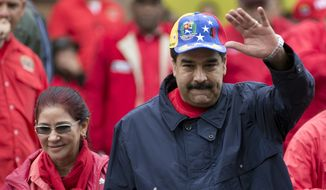 Venezuela's President Nicolas Maduro waves to supporters as he walks with first lady Cilia Flores during a labor Day march in Caracas, Venezuela, Sunday, May 1, 2016. President Maduro ordered a 30 percent increase in the minimum wage, the latest move by the socialist government to grapple with high inflation and economic stagnation. (AP Photo/Ariana Cubillos)