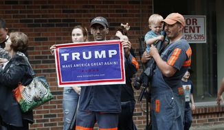 Coal miner Chris Steele holds a sign supporting Donald Trump outside a Democratic presidential candidate Hillary Clinton event in Williamson, W.V., Monday, May 2, 2016. (AP Photo/Paul Sancya)