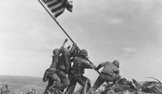 In this Feb 23, 1945 file photo, U.S. Marines of the 28th Regiment, 5th Division, raise the American flag atop Mt. Suribachi, Iwo Jima, Japan. The Marine Corps said Monday, May 2, 2016, that it has begun investigating whether it mistakenly identified one of the men shown raising the U.S. flag at Iwo Jima in one of the iconic images of World War II after two amateur history buffs began raising questions about the picture. (Associated Press)