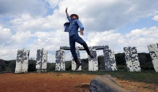 """Mark Cline does an impromptu leap before """"Foamhendge"""", his full-sized foam and fiberglass recreation of Stonehendge, located on Rt. 11 near Natural Bridge, Va., Tuesday, April 26, 2016. Cline must move the monument before Aug. 1 because Foamhenge sits on property that will become part of the new Natural Bridge State Park. (Bob Brown/Richmond Times-Dispatch via AP)"""