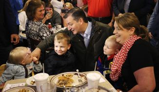 Republican presidential candidate, Sen. Ted Cruz, R-Texas, talks with Elizabeth Craig's children during a visits to the Bravo Cafe during a campaign stop, Monday, May 2, 2016, in Osceola, Ind. (AP Photo/Charles Rex Arbogast)