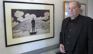 In this Friday, April 29, 2016 photo, attorney Bruce Rubenstein, a collector of left-wing political memorabilia, stands in front of a 1920s drawing by political cartoonist Art Young on April 29, 2016 inside his office in Hartford, Conn. Rubenstein is threatening to sue the University of Hartford which plans to sell a political memorabilia collection to which Rubenstein donated hundreds of items. (AP Photo/Pat Eaton-Robb)