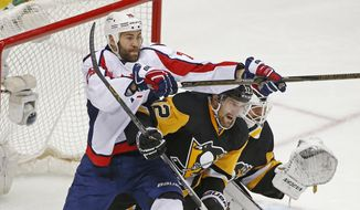 Washington Capitals Daniel Winnik (26) and Pittsburgh Penguins Ben Lovejoy (12) battle for position in front of the net while Pittsburgh Penguins goalie Matt Murray (30) looks fo the puck during the third period of Game 3 in an NHL hockey Stanley Cup Eastern Conference semifinals in Pittsburgh, Monday, May 2, 2016. (AP Photo/Gene J. Puskar)
