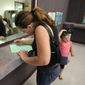 A woman fills out a form at the Sacramento (Calif.) County welfare office. (Associated Press)