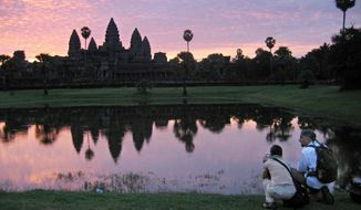 FILE - In this July 14, 2014 file photo, tourists look at the view of the Angkor Wat temples at sunrise, outside Siem Reap, Cambodia. The main road alongside Cambodia's famed Angkor Wat temple is now off-limits to cars as authorities seek to ease traffic jams at the site that draws 2.1 million tourists a year. The volume of cars driving near the temple has increased so dramatically in recent years it raised concerns that vibrations caused by the vehicles could harm the temples, built between the 9th and 15th centuries. (AP Photo/Anat Givon, File)