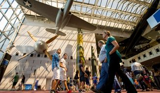 People walk in the Smithsonian National Air and Space Museum in Washington on April 19, 2015. (Associated Press) **FILE**