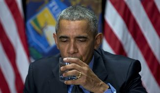 President Barack Obama drinks filtered Flint, Mich. water during a briefing on the response and recovery plans of the ongoing water crisis by the unified command group at the Food Bank of Eastern Michigan in Flint, Mich., Wednesday, May 4, 2016. (AP Photo/Carolyn Kaster)