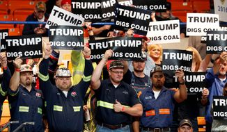 A group of coal miners wave signs for Republican presidential candidate Donald Trump as they wait for a rally in Charleston, West Virginia, on Thursday. (Associated Press)