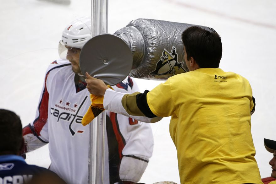 A Pittsburgh Penguins fan waves an inflatable Stanley Cup at Washington Capitals' Alex Ovechkin, left, during the third period of Game 4 in an NHL hockey Stanley Cup Eastern Conference semifinals in Pittsburgh, Wednesday, May 4, 2016. (AP Photo/Gene J. Puskar)