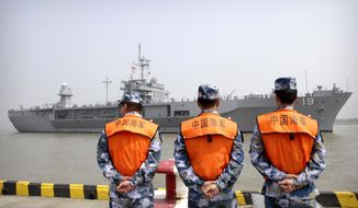 Soldiers from the Chinese People's Liberation Army (PLA) Navy watch as the USS Blue Ridge arrives at a port in Shanghai, Friday, May 6, 2016. The commander of the U.S. Navy's 7th Fleet has dismissed the cancellation of a planned port visit to Hong Kong by an American aircraft carrier as a minor hurdle in relations between the two militaries. (AP Photo)