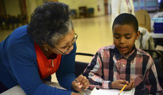 ADVANCE FOR WEEKEND EDITIONS - In this April 12, 2016 photo, teachers aid Jennifer Waller helps Tyshawn Kennedy, 9, with his writing skills during Boys-2-Men, an after-school program at the Family Life Center at the Church in the Round in Aliquippa, Pa. (Lucy Schaly/Beaver County Times via AP) MANDATORY CREDIT