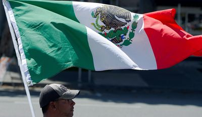 Vincent Flores waves a Mexican flag in a protest Saturday against presumptive Republican presidential nominee Donald Trump in Spokane, Washington. (The Spokesman-Review via Associated Press)