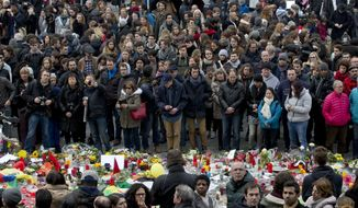 People gathered to observe a minute of silence and mourn for the victims of the bombings at the Place de la Bourse in the center of Brussels, Belgium, on March 24. (Associated Press)