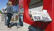 In this Saturday April 23, 2016, photo, petition signature gatherer Peter Keyes, right, discusses a petition to legalize marijuana, in Sacramento, Calif. It's a banner year in California for paid signature-gathers, like Keyes. (AP Photo/Rich Pedroncelli)