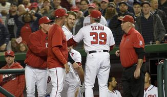 Washington Nationals' Bryce Harper, center, is restrained by bench coach Chris Speier, left, pitching coach Mike Maddux, second from left, and hitting coach Rick Schu (39) after Harper was ejected in the dugout during the ninth inning of an interleague baseball game against the Detroit Tigers, Monday, May 9, 2016, in Washington. The Nationals won 5-4. (AP Photo/Nick Wass)