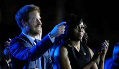 Britain's Prince Harry, left, and first lady Michelle Obama listen to speakers during the opening ceremony for the Invictus Games, Sunday, May 8, 2016, in Kissimmee, Fla. (AP Photo/John Raoux)