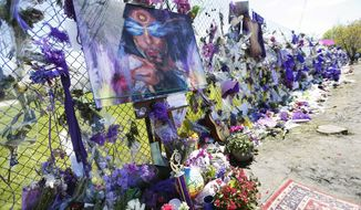 A painting of Prince is displayed on an easel at the flower-covered fence at Paisley Park Studios on May 2 in Chanhassen, Minn., where pop rock singer Prince died on April 21. (Associated Press)