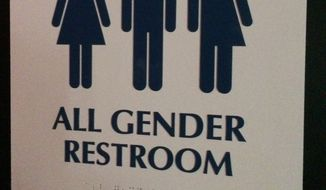 """This May 11, 2014, file photo shows an """"All Gender Restroom"""" sign outside a bathroom in a bar in Washington. Confrontations have flared across the country over whether to protect or curtail the right of transgender people to use public restrooms in accordance with their gender identity. (AP Photo) ** FILE **"""