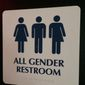 "An ""All Gender Restroom"" sign hangs outside a bathroom in a bar in Washington. Confrontations have flared across the country over whether to protect or curtail the right of transgender people to use public restrooms in accordance with their gender identity. (Associated Press)"
