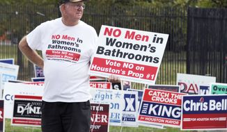 FILE - In this Wednesday, Oct. 21, 2015 file photo, a demonstrator holds a sign against the Houston Equal Rights Ordinance outside an early voting center in Houston. The contested ordinance is a broad measure that would consolidate existing bans on discrimination tied to race, sex, religion and other categories in employment, housing and public accommodations, and extend such protections to gays, lesbians, bisexuals and transgender people. The anti-bias ordinance was repealed in a November 2015 referendum. (AP Photo/Pat Sullivan)