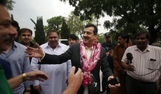 Pakistan's former Prime Minister Yusuf Raza Gilani, center, being greeted by supporters at outside his residence in Islamabad, Pakistan, Tuesday, May 10, 2016. A joint raid by U.S. and Afghan forces on Tuesday rescued his son who was held captive for three years by Islamic militants, officials said. Ali Haider Gilani was found during the raid near Afghanistan's eastern border with Pakistan, according to a spokesman for Afghan President Ashraf Ghani. (AP Photo/Anjum Naveed)