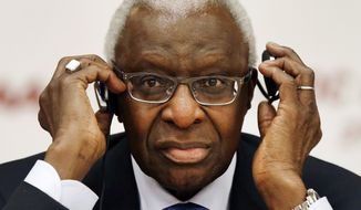 In this Aug. 21, 2015, file photo, then-IAAF president Lamine Diack adjusts his headphones during a joint IOC and IAAF news conference on the site of the World Athletic Championships in Beijing. (AP Photo/Kin Cheung, File)