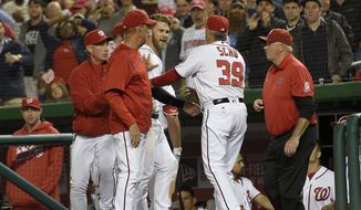 Washington Nationals' Bryce Harper, center, is restrained by pitching coach Mike Maddux, left, bench coach Chris Speier, far left, and hitting coach Rick Schu (39) after Harper was ejected in the dugout during the ninth inning of an interleague baseball game against the Detroit Tigers, Monday, May 9, 2016, in Washington. The Nationals won 5-4. (AP Photo/Nick Wass)