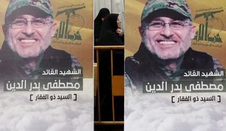 """Pictures of slain top commander Mustafa Badreddine, who was killed in Syria, hang during his funeral procession in a southern suburb of Beirut, Lebanon, Friday, May 13, 2016. Badreddine died in an explosion in Damascus, a death that is a major blow to the Shiite group, which has played a significant role in the conflict next door. Arabic reads, """"The martyr commander Mustafa Badreddine.""""(AP Photo/Hassan Ammar)"""