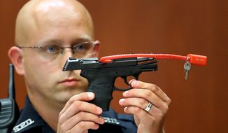 In this June 28, 2013, file photo, Sanford police officer Timothy Smith holds up the gun that was used to kill Trayvon Martin, while testifying in the George Zimmerman trial, in Seminole circuit court in Sanford, Fla. The pistol former neighborhood watch volunteer Zimmerman used in the fatal shooting of Martin is going up for auction online. (AP Photo/Orlando Sentinel, Joe Burbank, Pool, File)