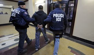 Immigration and Customs Enforcement officers escort an arrestee during a series of early-morning raids on March 3, 2015, in the Bronx borough of New York. (Associated Press)